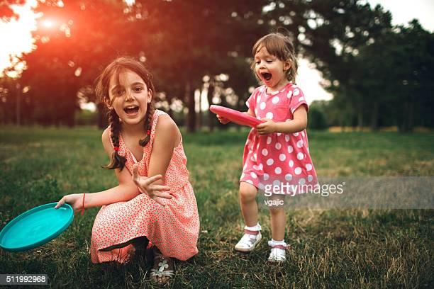 姉妹フリスビーで遊ぶ 2 つのピクニック