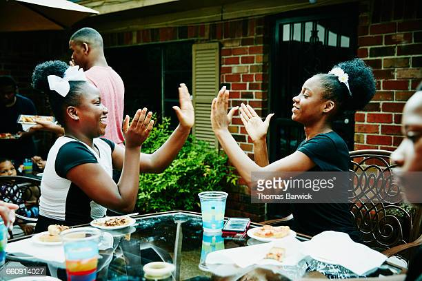 Two sisters playing game during family party
