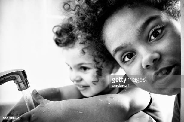 two sisters playing in the bathroom. - onebluelight stock pictures, royalty-free photos & images