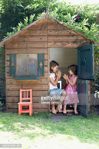 Two sisters (4-7) playing in wendy house in garden, smiling