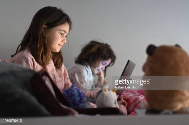 two sisters playing on laptops and tablet in bed - rafael ben ari stock-fotos und bilder