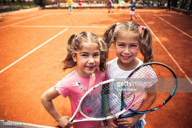 two sisters playing tennis - doubles stock pictures, royalty-free photos & images