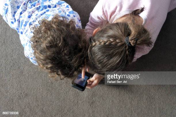 Two sisters playing together on a mobile phone application