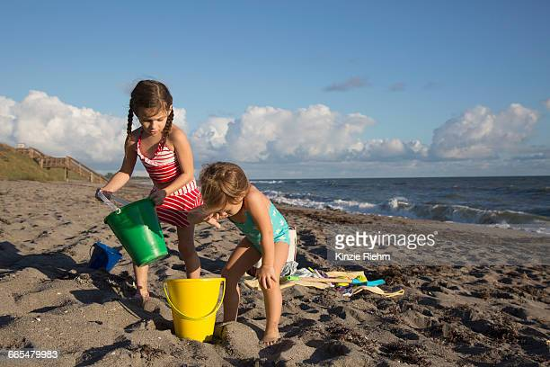 two sisters playing with toy buckets on beach, blowing rocks preserve, jupiter island, florida, usa - jupiter island stock photos and pictures