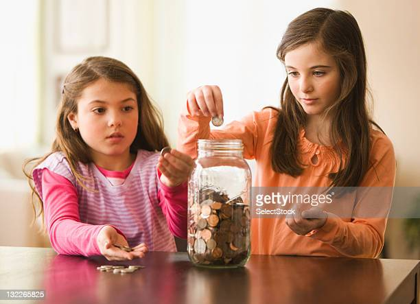 Two Sisters putting coins in a jar