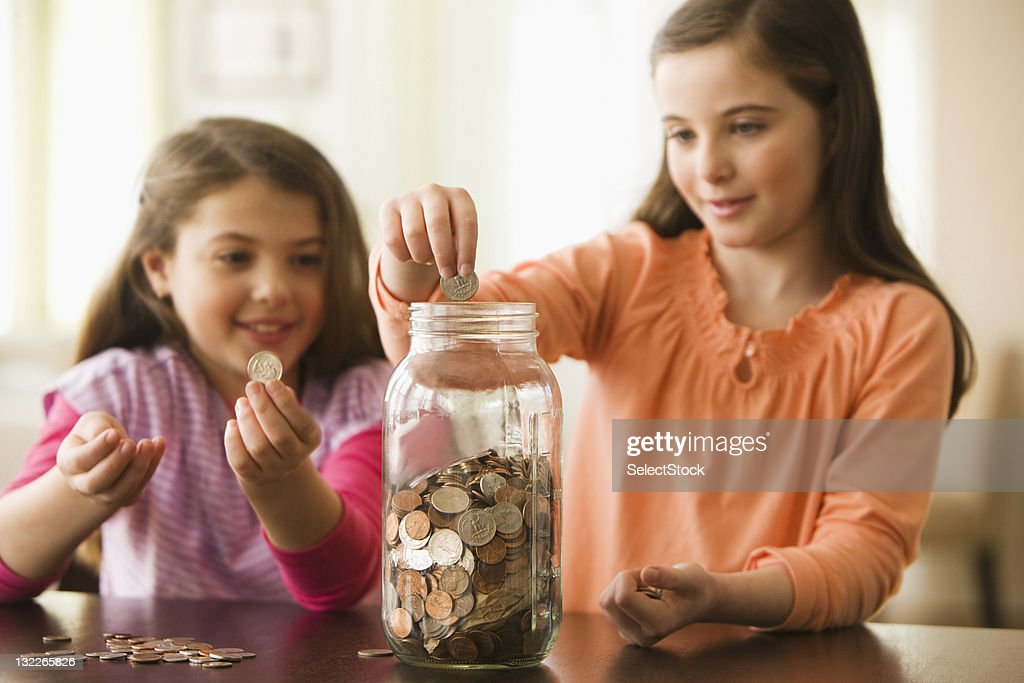 Two Sisters putting coins in a jar : Stock Photo