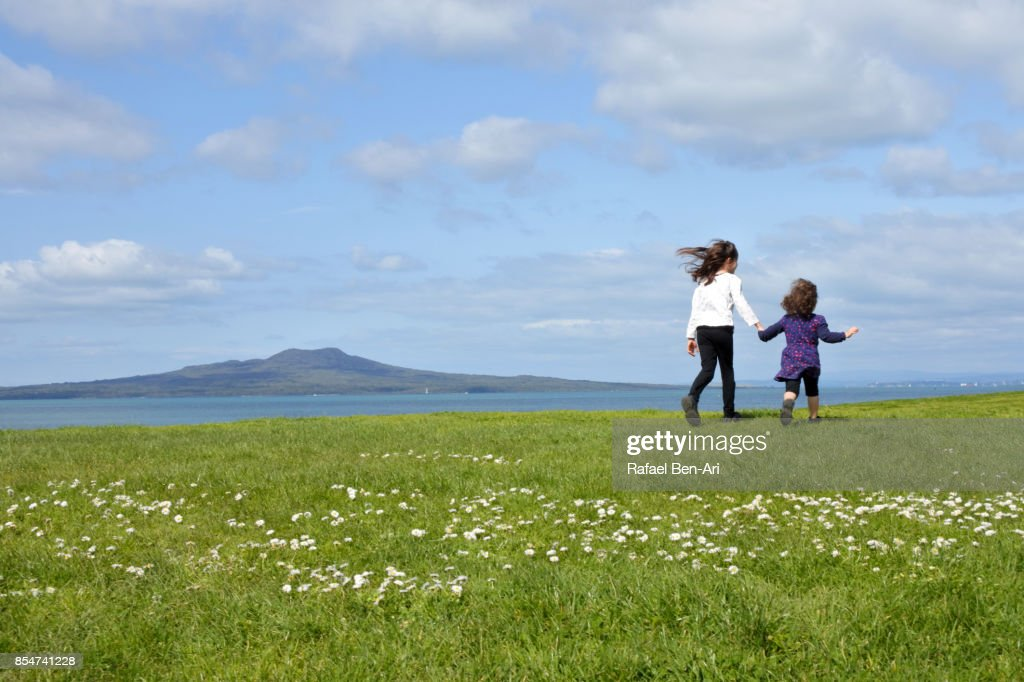 Two sisters running together outdoors on a green field : Stock Photo
