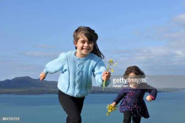 two sisters running together outdoors - rafael ben ari photos et images de collection