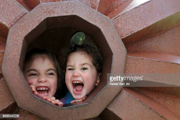 Two sisters scream together outdoors