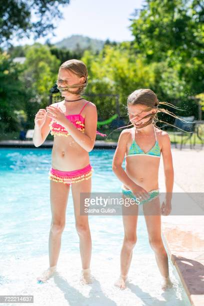 Two sisters shaking wet hair by outdoor swimming pool