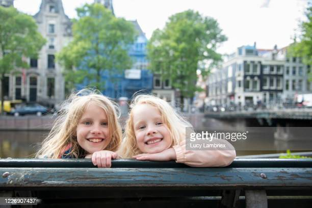 two sisters side by side on a bench, out on a city trip in amsterdam - lucy lambriex stockfoto's en -beelden
