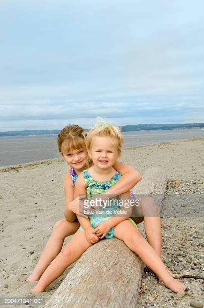 Two sisters (3-6) sitting atop driftwood on beach, portrait
