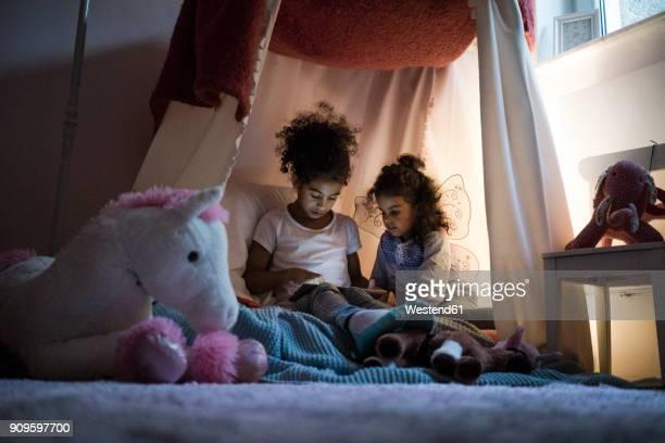 Two sisters sitting in dark children's room, looking at digital tablet