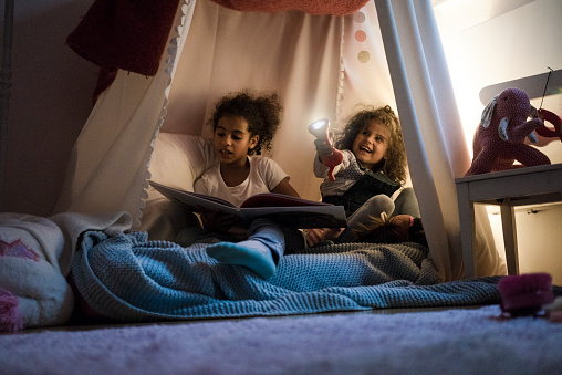 Two sisters sitting in dark children's room, playing with torch, reading book - gettyimageskorea