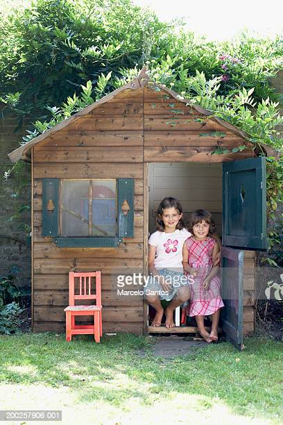 Two sisters (4-7) sitting in wendy house, smiling, portrait