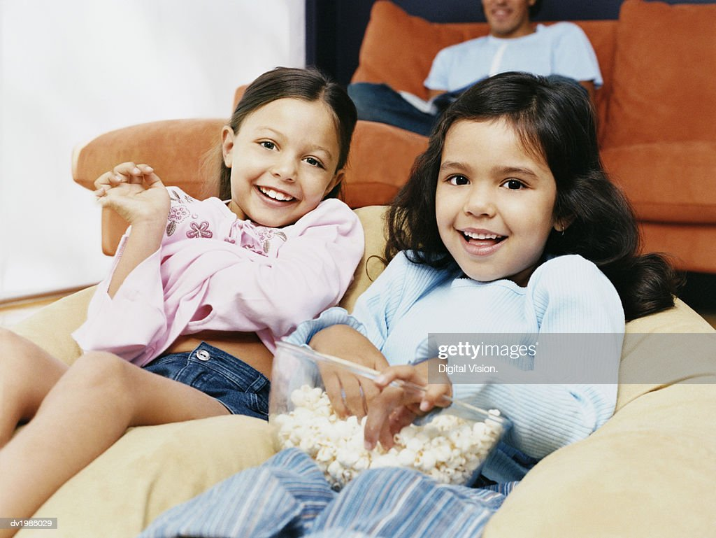 Two Sisters Sitting on a Beanbag With a Bowl of Popcorn : Stock Photo