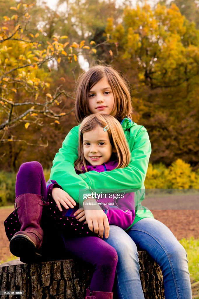 two sisters sitting on a tree trunk : Stock Photo