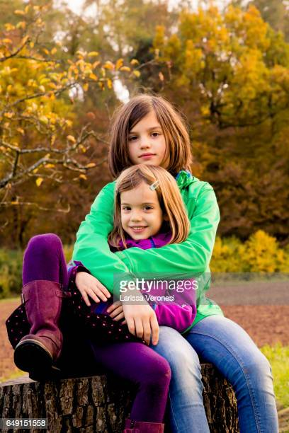 two sisters sitting on a tree trunk - larissa veronesi stock pictures, royalty-free photos & images