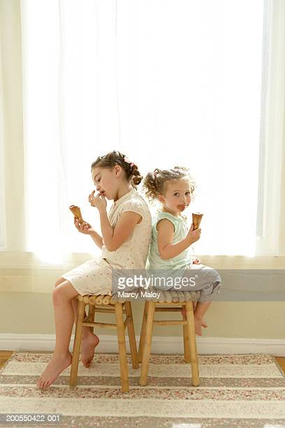 Two sisters (2-6) sitting on stools, eating ice cream cones, side view