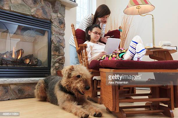Two sisters, teenager girls, and dog in living room