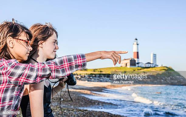 Two sisters, teenager girls, exploring ocean with binocular