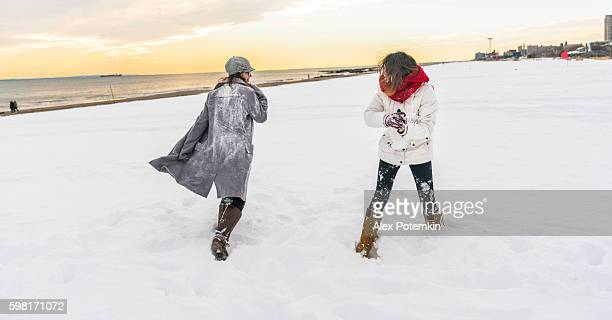 Two sisters, teenager girls, play snowballs at the Brighton Beach