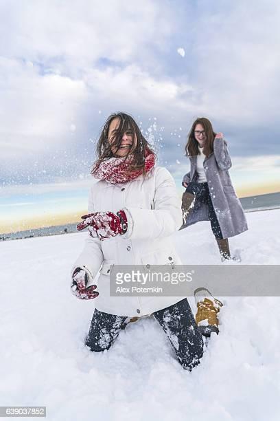 Deux sœurs, adolescent fille, jeu de boules de neige sur la plage de Brighton