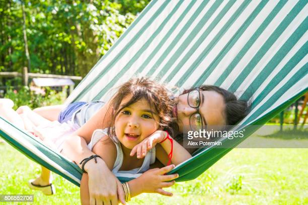 Two sisters, the 5-years-old little girl and 15-years-old teenager, resting in the hammock at the backyard