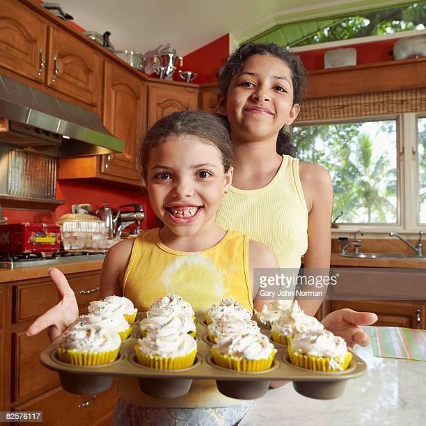 Two sisters togther one holds baking tray