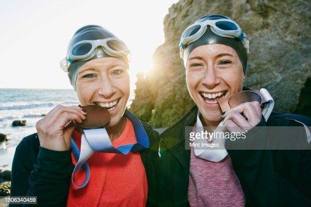 two sisters, triathletes in training in swimwear, swimhats and goggles wearing their large medals, winners. - medallist stock pictures, royalty-free photos & images