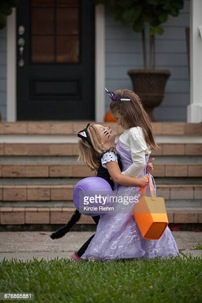 two sisters trick or treating in cat and fairy costumes hugging at porch stairway - cat costume stock photos and pictures