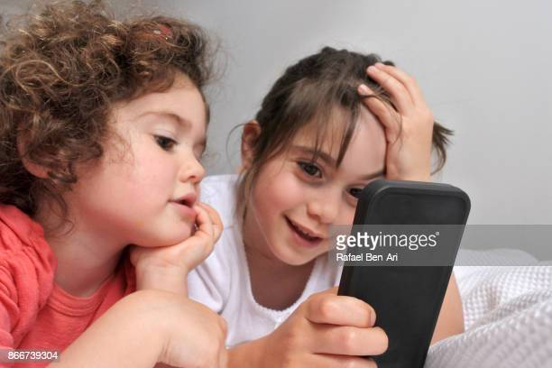 Two sisters watching together a video clip on a mobile phone