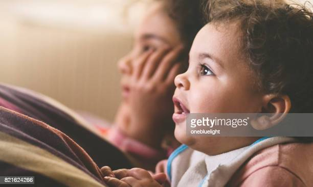 two sisters watching tv - onebluelight stock pictures, royalty-free photos & images