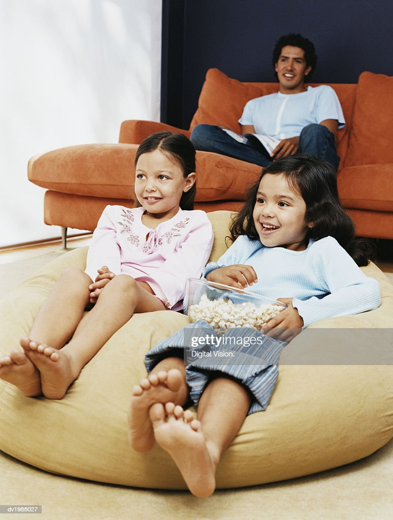 Two Sisters Watching TV With Their Father in Their Living Room : Stock Photo