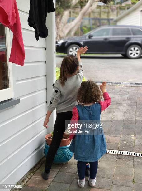 two sisters waving goodbye to their relatives - rafael ben ari stock pictures, royalty-free photos & images