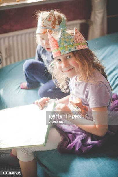 two sisters wearing crowns and unpacking presents on bed - happybirthdaycrown stock pictures, royalty-free photos & images