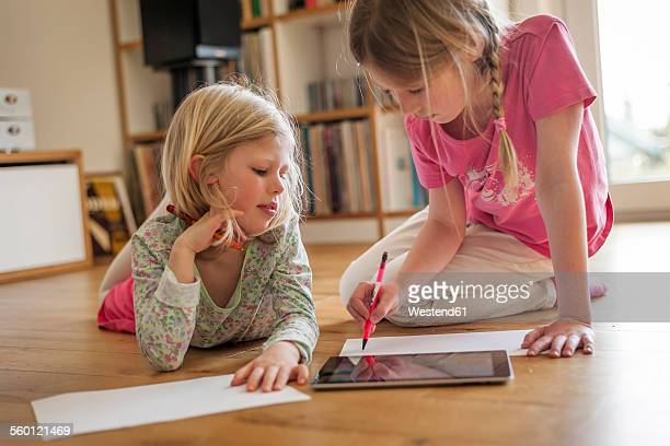Two sisters with digital tablet and sheets of paper on floor