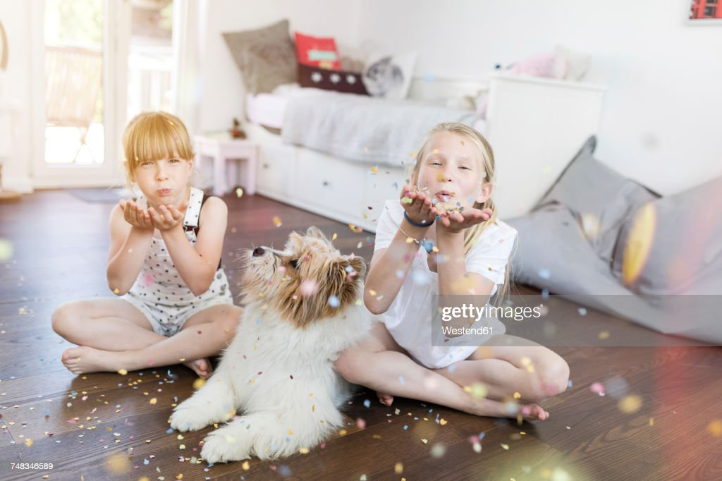 Two sisters with dog at home blowing confetti : Stock Photo