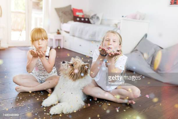 Two sisters with dog at home blowing confetti