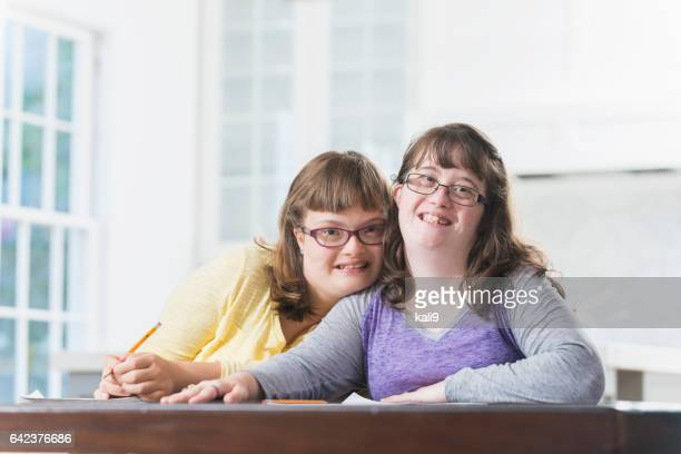 Two sisters with down syndrome, doing homework