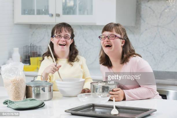 Two sisters with down syndrome, in the kitchen