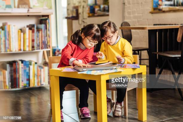 Two sisters with Down syndrome sitting at the table in kindergarten