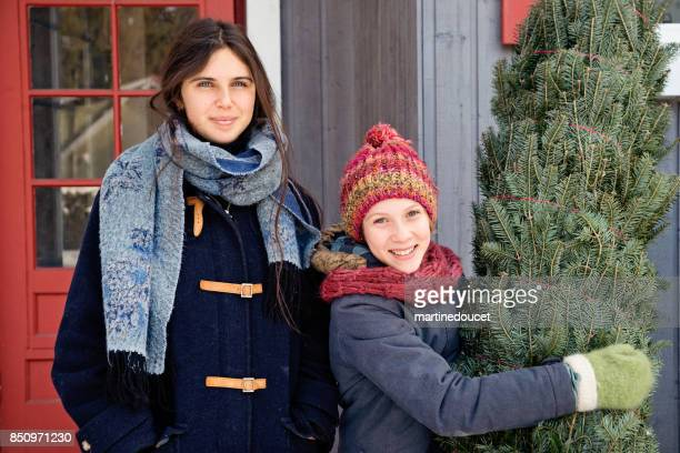 two sisters with freshly cut christmas tree in front of house outdoors. - 12 17 months stock pictures, royalty-free photos & images