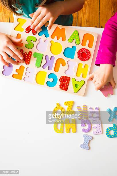 Two sisters with with wooden alphabet puzzle