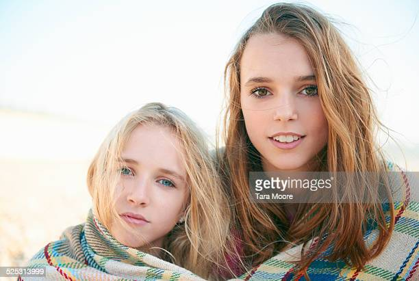two sisters wrapped in blanket together