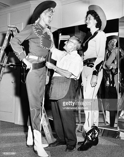 Two six foot three inch tall women are fitted in cowboy gear by a short tailor for promoting the film 'The Big Country' Hollywood California August...