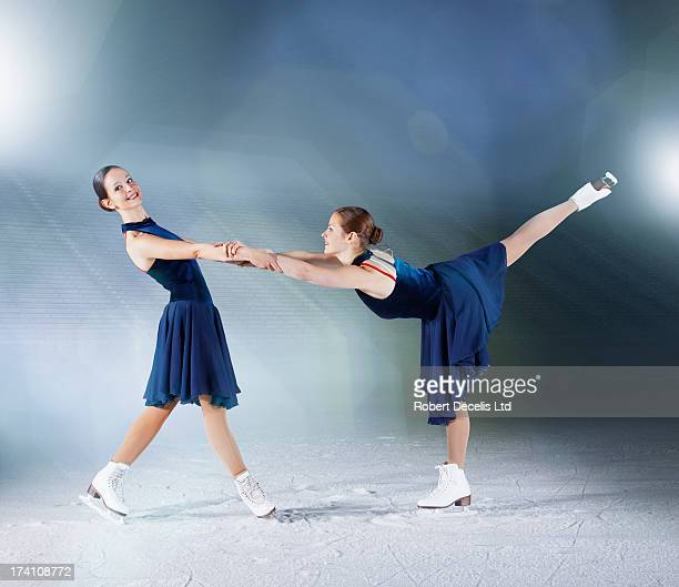 two skaters, one supporting the other. - ice skating stock pictures, royalty-free photos & images