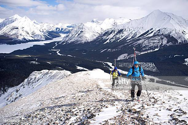 two skiers hike snowy ridge in the mountains - kananaskis stock-fotos und bilder