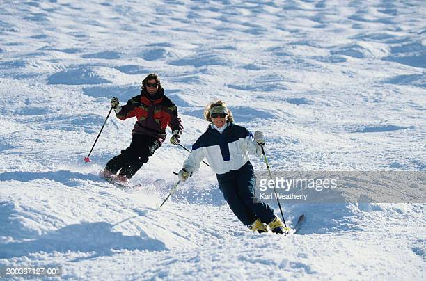 Two skiers in moguls