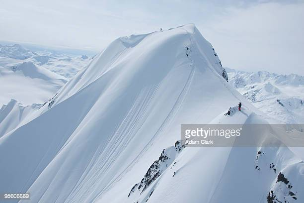 Two skiers on a snowy mountain getting ready to drop in Haines, Alaska.